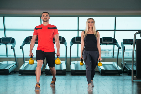 Young Woman And Man Doing Exercise With Kettle Bell In The Gym Stock Photo