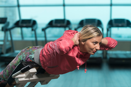 Young Fitness Woman Working Out Back On Roman Chair In Fitness Center