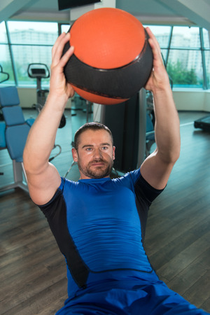 Young Fitness Man Working Out Abs With Fitness Ball On Adjustable Bench In Gym Center