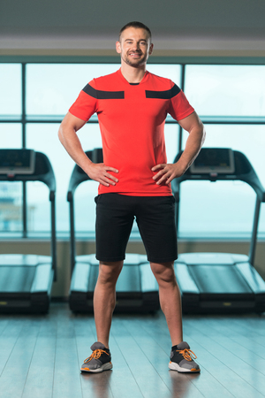 Portrait Of Handsome Personal Trainer Wearing Sportswear In Fitness Center Gym Standing Strong