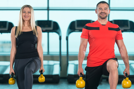 kettle bell: Young Woman And Man Doing Exercise With Kettle Bell In The Gym Stock Photo
