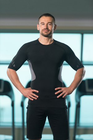 physique: Portrait Of Handsome Personal Trainer Wearing Sportswear In Fitness Center Gym Standing Strong