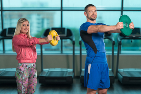 Young Woman And Men Doing Exercise With Weights In The Gym Stock Photo