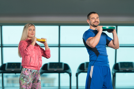 Young Woman And Men Doing Exercise With Weights In The Gym Foto de archivo