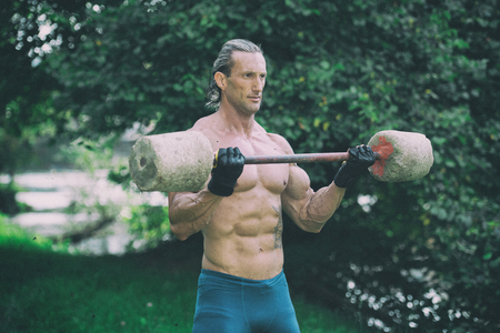 Muscular Adult Man Doing A Exercise For Biceps With Made Hand Barbell Outdoors Workout Stock Photo