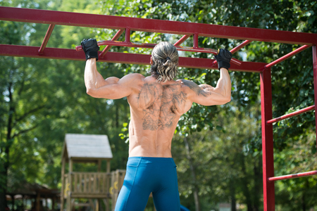 Muscular Built Athlete Working Out In An Outdoor Gym - Doing Chin-Ups