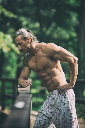 Hübscher reifer Mann, der stark draußen in der Natur steht und Muskeln biegt - muskulöser athletischer Bodybuilder-Eignungs-Modell, das nach Übungen aufwirft Standard-Bild - 80424877