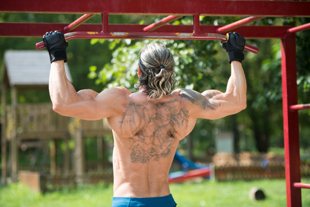 physique: Muscular Built Athlete Working Out In An Outdoor Gym - Doing Chin-Ups