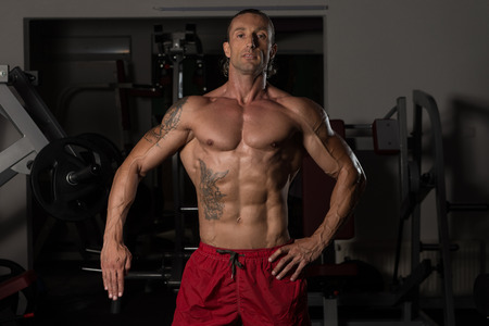 physique: Handsome Mature Man Standing Strong In The Gym And Flexing Muscles - Muscular Athletic Bodybuilder Fitness Model Posing After Exercises