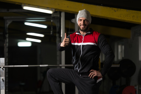 build up: Portrait Of A Physically Fit Man In Track Suit Resting His Well Trained Body Showing Thumbs Up - Muscular Athletic Bodybuilder Fitness Model Posing After Exercises