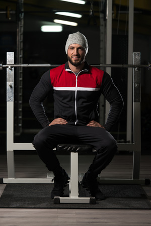 physically fit: Portrait Of A Physically Fit Man In Track Suit Resting His Well Trained Body - Muscular Athletic Bodybuilder Fitness Model Posing After Exercises Stock Photo