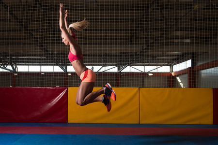 CHALLENGING: Female Athlete Performing a Long Jump in Gym - One of the Best Jumping Exercise for Vitality