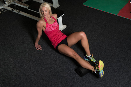 roller: Muscular Woman Stretches With Roller At The Floor In A Gym And Flexing Muscles - Muscular Athletic Bodybuilder Fitness Model