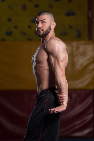 Giovane Bello Essere forti in palestra e che flette i muscoli - Muscoloso Athletic bodybuilder Posizione di modello dopo le esercitazioni Archivio Fotografico - 80683398