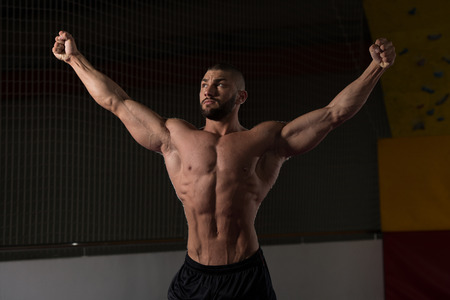 physically fit: Portrait Of A Young Physically Fit Man Showing His Well Trained Body - Muscular Athletic Bodybuilder Fitness Model Posing After Exercises Stock Photo