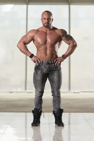 Healthy Young Tattoo Man Standing Strong In Pants And Flexing Muscles - Muscular Athletic Bodybuilder Fitness Model Posing After Exercises Stock Photo