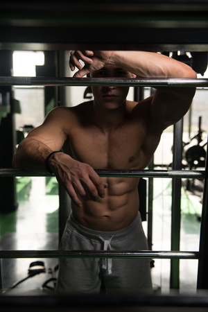 physically fit: Muscular Man Resting After Exercises - Portrait Of A Physically Fit Young Man In Gym