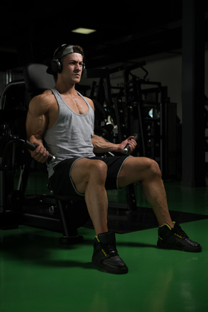 Young Bodybuilder Doing Heavy Weight Exercise For Biceps On Machine