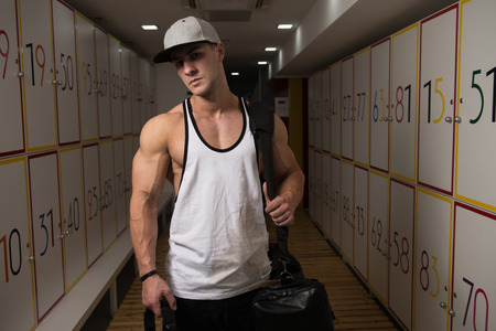 Young Fit Adult Man Changing Clothings In Locker Room Of Gym Facility 版權商用圖片