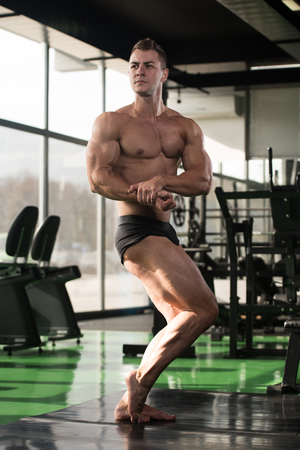 iron man: Handsome Young Man Standing Strong In The Gym And Flexing Muscles - Muscular Athletic Bodybuilder Fitness Model Posing After Exercises Stock Photo