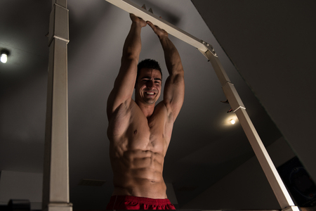 physically fit: Portrait Of A Young Physically Fit Man Showing His Well Trained Abdominal Muscle - Muscular Athletic Bodybuilder Fitness Model Posing After Exercises