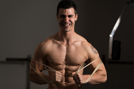 Handsome Man Standing Strong In The Gym And Flexing Muscles With Cable - Muscular Athletic Bodybuilder Fitness Model Posing After Exercises