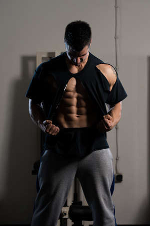 Handsome Man Standing Strong In The Gym And Ripping the T-Shirt Off - Muscular Athletic Bodybuilder Fitness Model Posing After Exercises