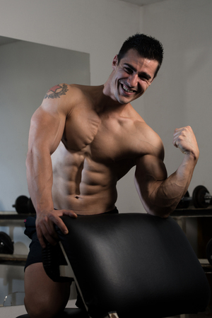 physically fit: Muscular Man Resting After Exercises - Portrait Of A Physically Fit Young Man Without A Shirt