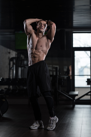 Portrait Of A Young Physically Fit Man Showing His Well Trained Body - Muscular Athletic Bodybuilder Fitness Model Posing After Exercises Stock Photo