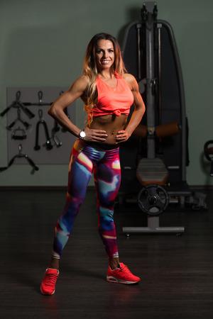 Portrait Einer Körperlich fit Frau sie gut trainierter Körper angezeigt - Muskulöser athletischer Bodybuilder Fitness Model Posing nach Übungen Standard-Bild