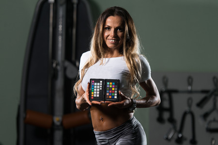 Fitness Woman Showing Color Checker - Equipment Of Professional Photographer For Adjust And Balance Photograph Stock Photo