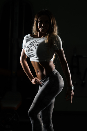 Silhouette Fitness Woman Standing Strong In The Gym And Flexing Muscles - Muscular Athletic Bodybuilder Model Posing After Exercises