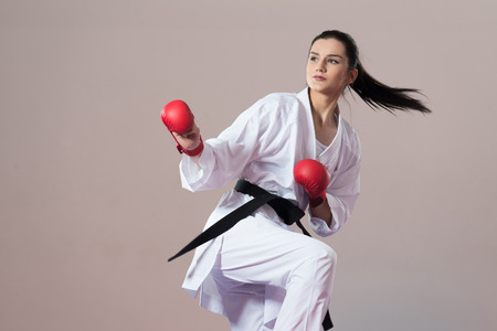 Junge Frau übt ihre Karate Moves - White Kimono - Black Belt