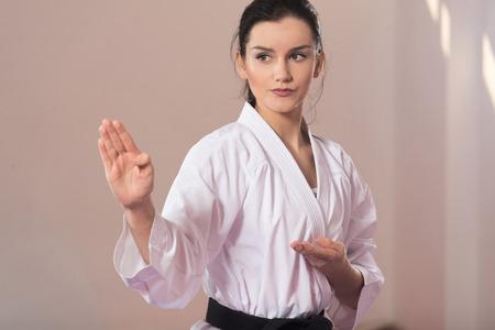 젊은여자가 그녀의 가라테 이동 연습 - 화이트 기모노 - 블랙 벨트