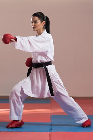 Ung kvinna som utövar sin karateflyttning - Vit Kimono - Svart Bälte Stockfoto