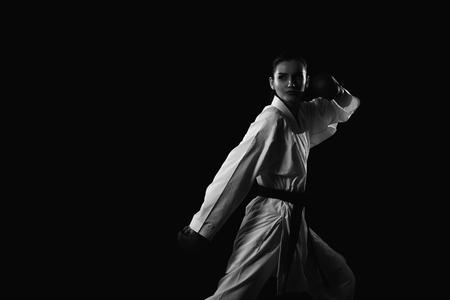 jujitsu: Young Muslim Woman In Traditional Kimono Practicing Her Karate Moves - Isolated On Black Background