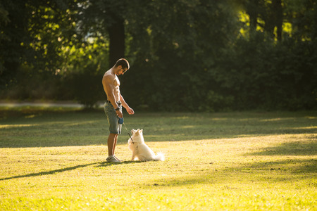 Naked Young Man Holding Dog German Spitz In Park - Together Enjoying The View