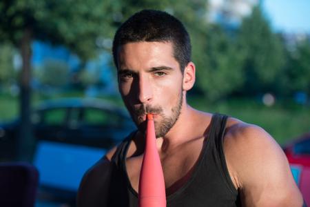 Young Man Smoking Shisha Outdoors - Man Exhaling Smoke Inhaling From A Hookah Stock Photo