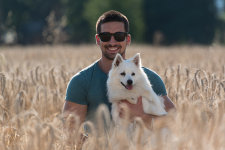 harvested: Young Man Sitting With Dog German Spitz In Harvested Field
