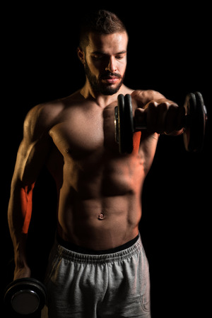 Young Man Working Out Shoulders With Dumbbells On Black Background