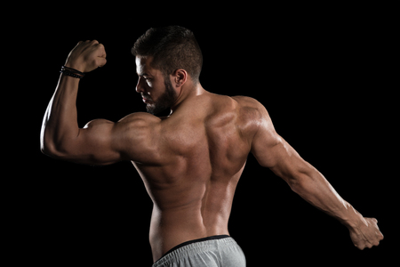 Young Athlete Flexing Muscles - Isolate On Black Blackground - Copy Space Stock Photo