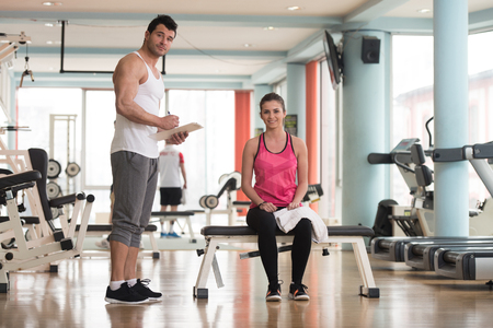 Personal Trainer Takes Notes While Young Woman Resting On Bench In Gym