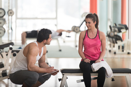 energy work: Personal Trainer Takes Notes While Young Woman Resting On Bench In Gym