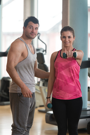 energy work: Personal Trainer Showing Young Woman How To Train Shoulder Exercise With Dumbbells In A Gym Stock Photo