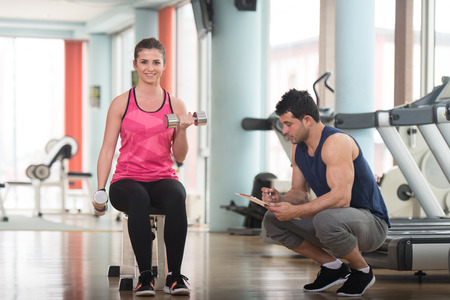 Personal Trainer Showing Young Woman How To Train Biceps Exercise With Dumbbells In A Health And Fitness Concept