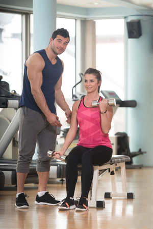 energy work: Personal Trainer Showing Young Woman How To Train Biceps Exercise With Dumbbells In A Health And Fitness Concept