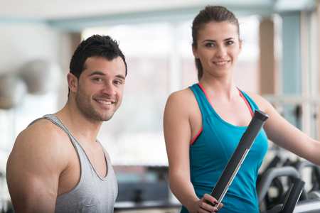 Group Of People Exercising On Elliptical Walker In Gym Or Fitness Club While Personal Trainer With Clipboard Watching Them - Group Of Woman And Men Exercising To Gain More Fitness