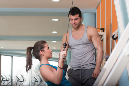 Personal Trainer Showing Ok Sign To Client - Young Woman Exercising Her Back On Machine In The Gym