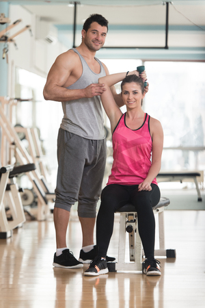 Personal Trainer Showing Young Woman How To Train Triceps Exercise With Dumbbell In A Health And Fitness Concept