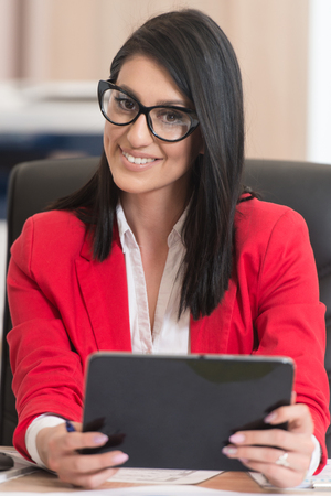 Portrait Of A Young Business Woman Using A Computer In The Office Stock Photo